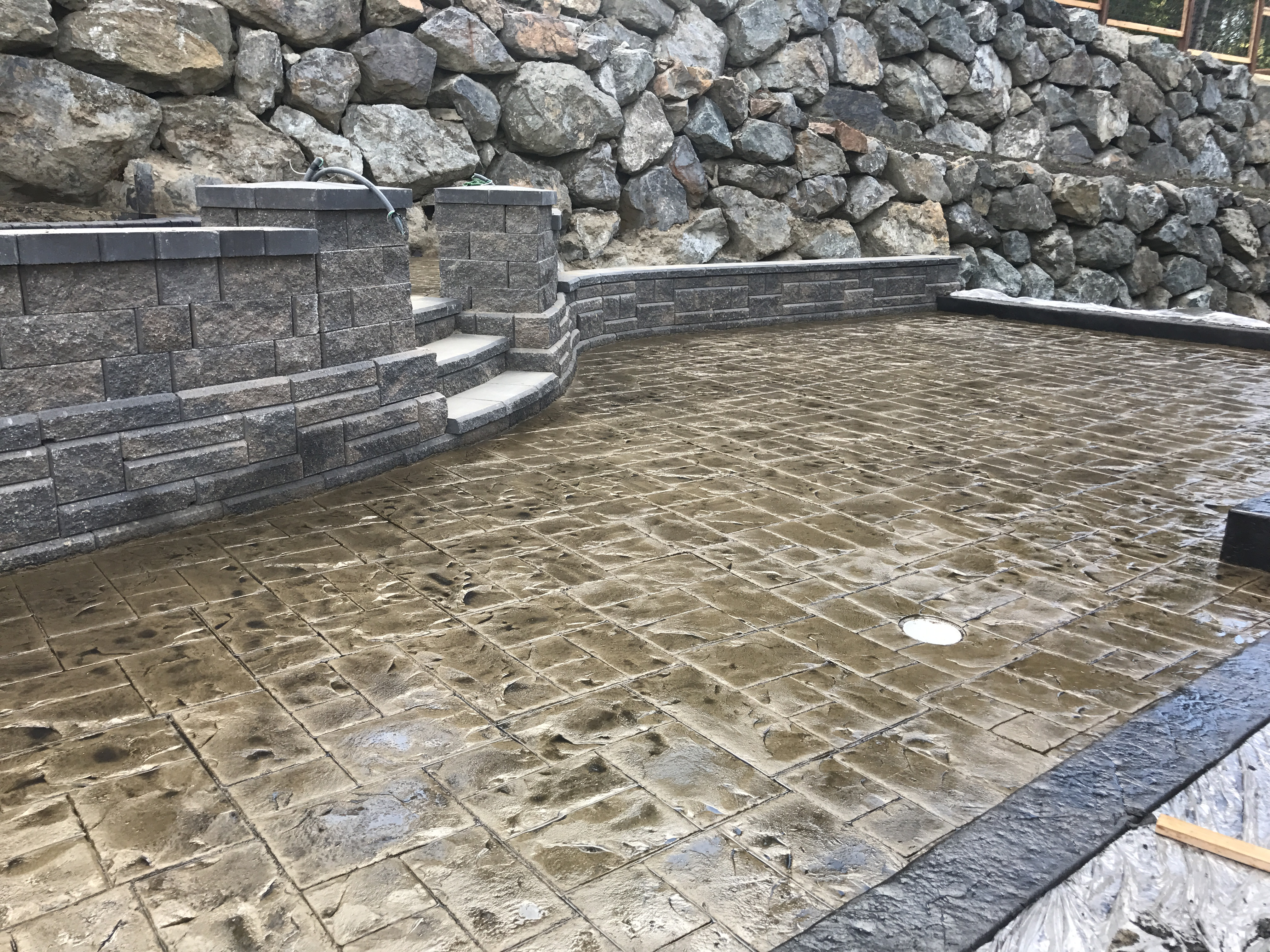 A photo of a backyard patio with retaining walls.