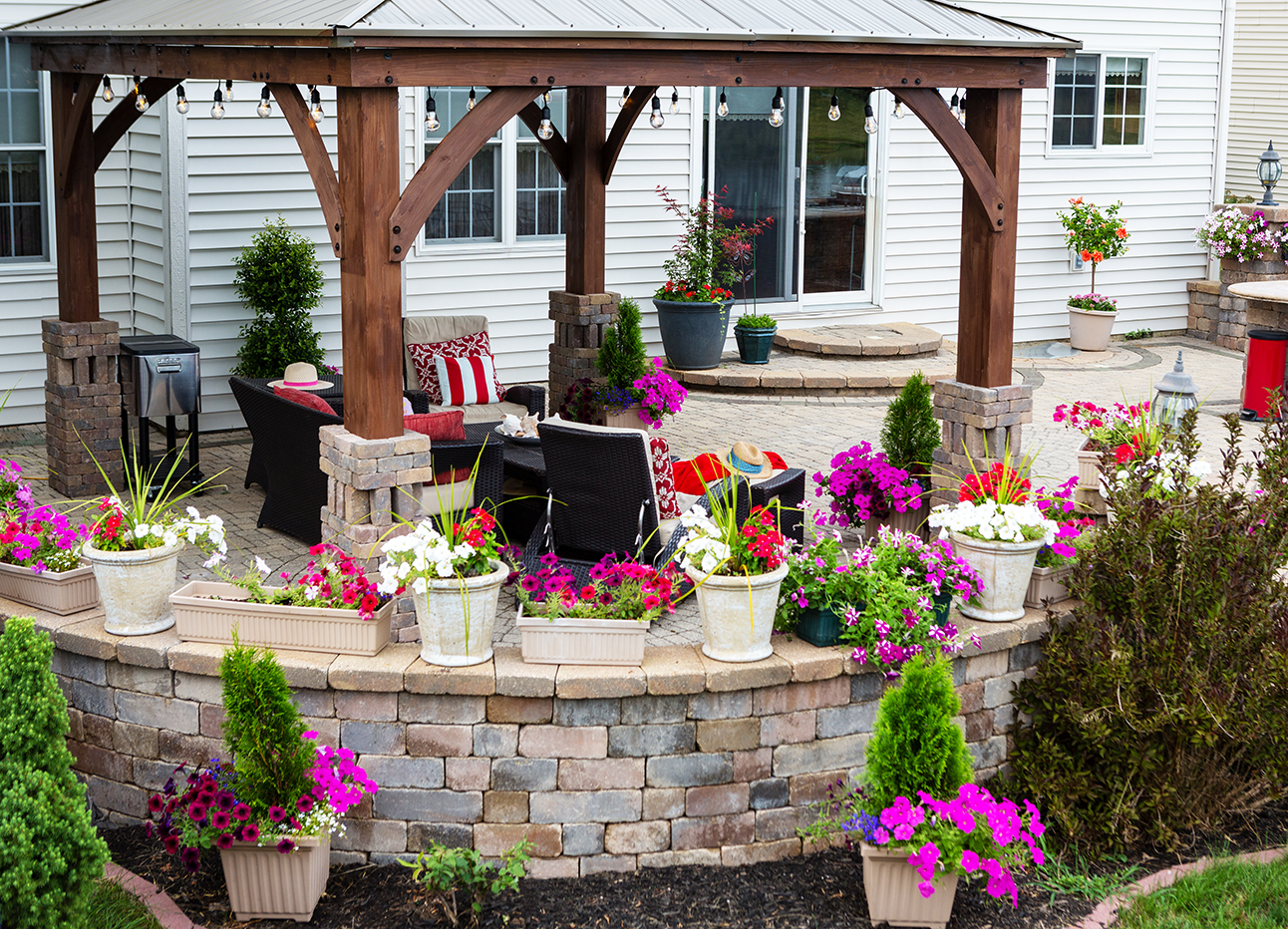A photo of a backyarrd patio with a pergola and lots of flowers.