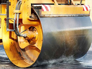 A photo of a paver smoothing asphalt.