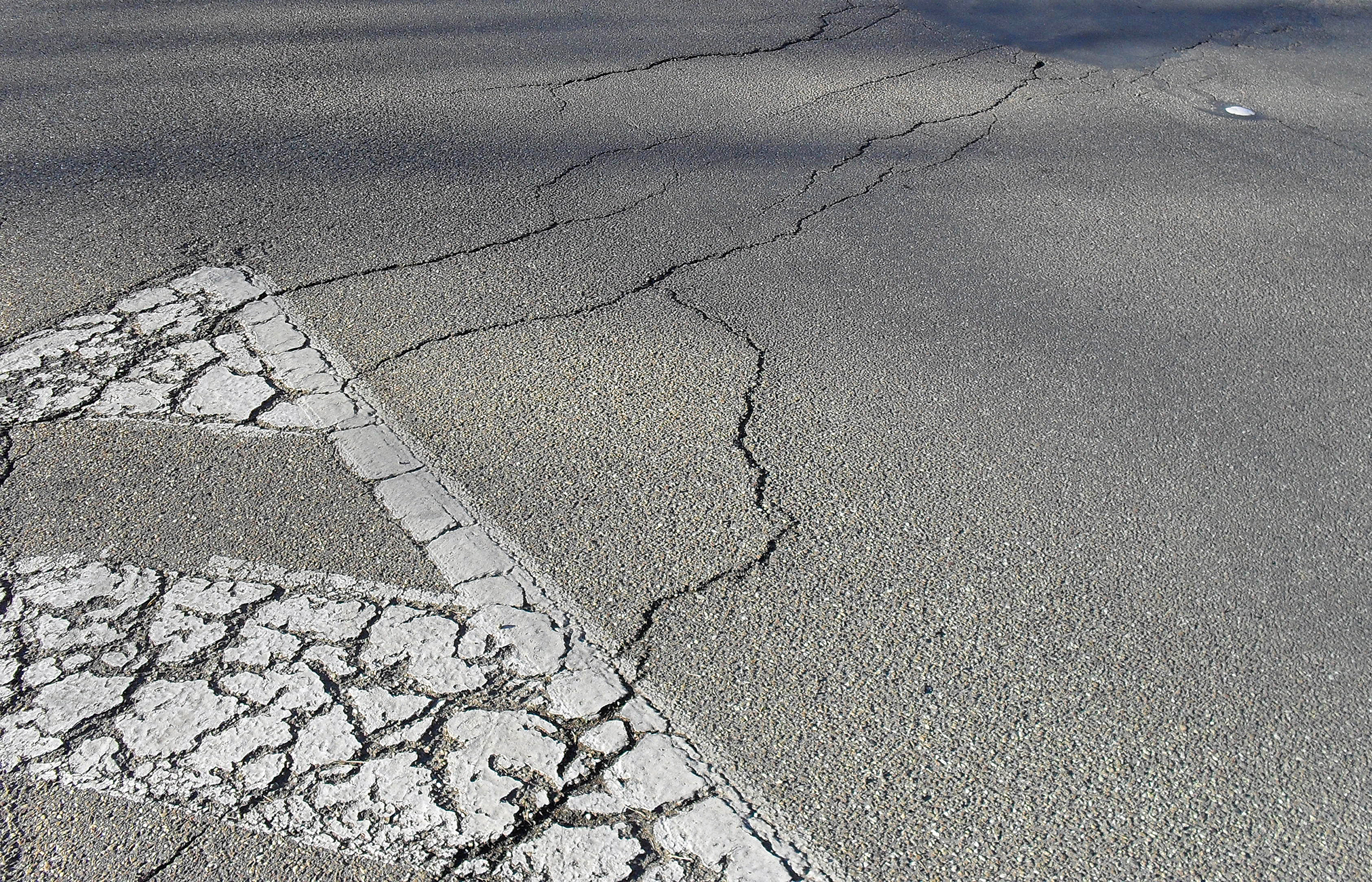 A photo of cracked asphalt.
