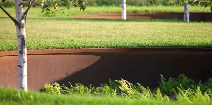 A retaining wall made of metal, with grass growing on top.