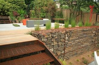 A rock retaining wall next to metal stairs leading up to a patio with seating.