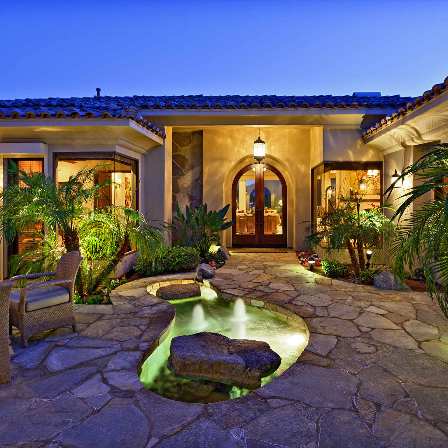 A photo of a backyard with tropical landscaping and a water feature.