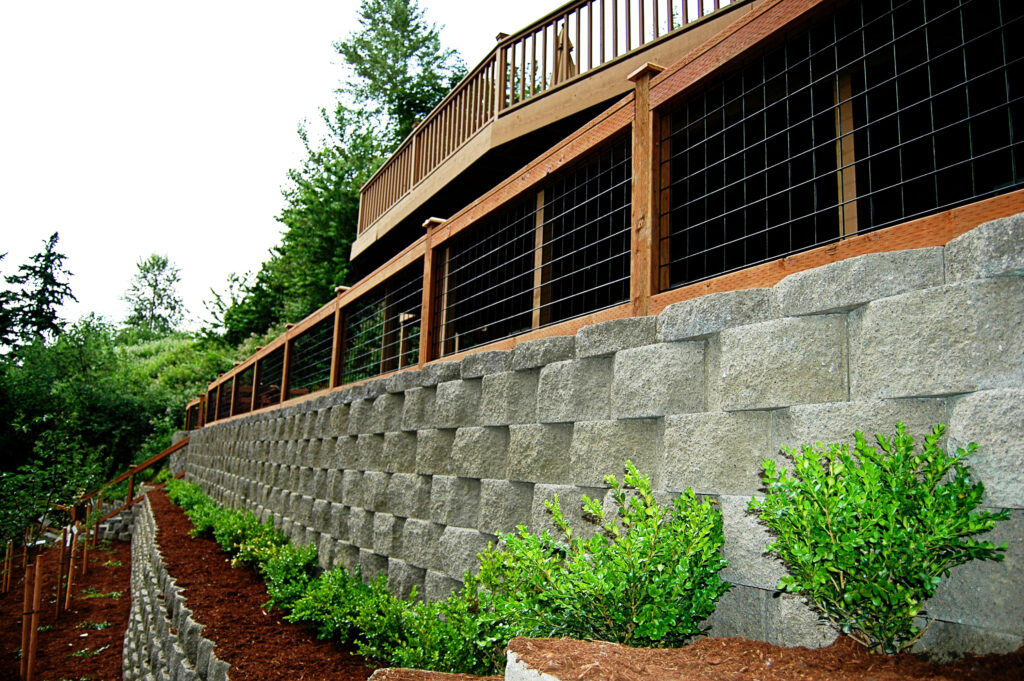 A photo of plants put in near a tiered retaining wall.