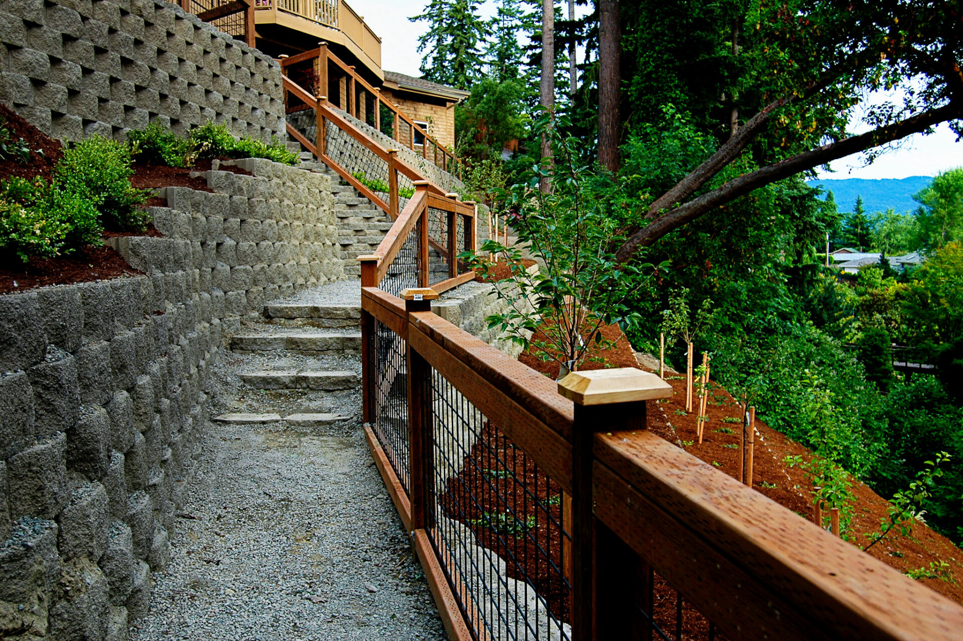 A photo of retaining walls and stairs with a fence leading uphill.