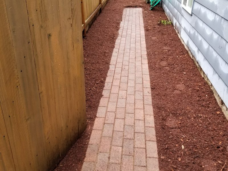 A photo of a yard with new mulch and a strip of red bricks.