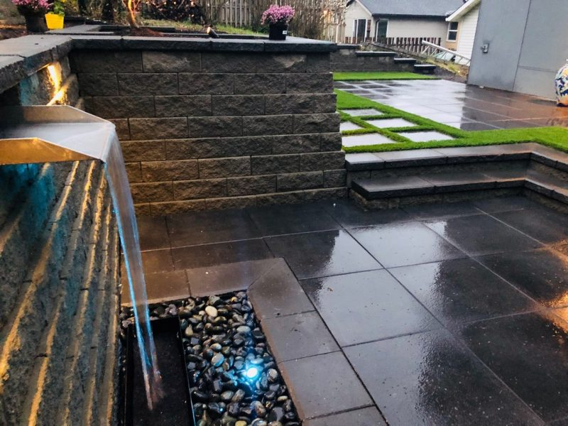 A backyard patio with a retaining wall and water feature.