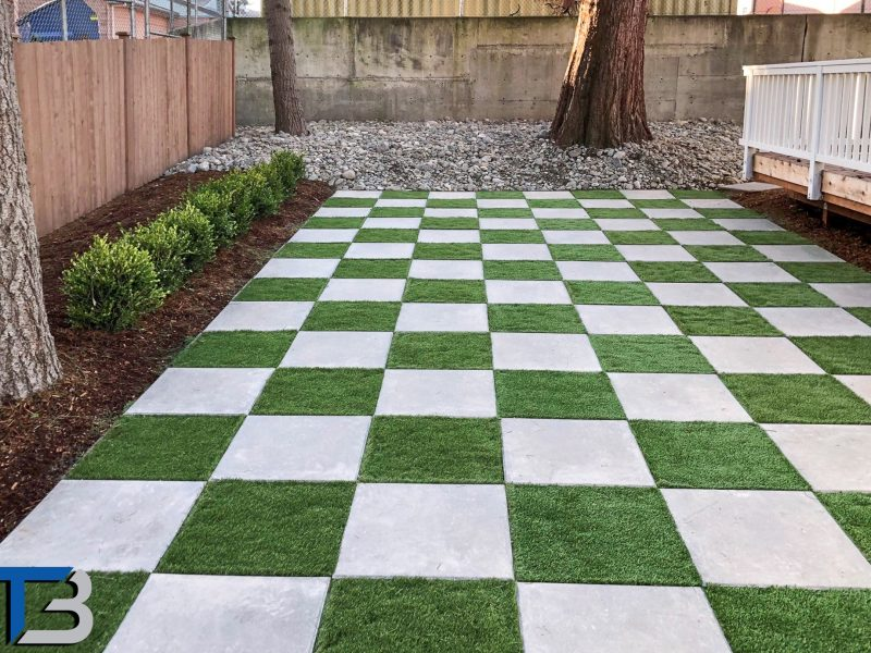 A photo of a backyard with a checkerboard lawn done with grass and concrete.